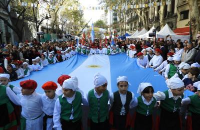 Dantzaris from the Euskal Echea school carrying huge Basque and Argentine flags