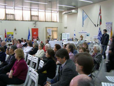 Público reunido en la Primera Muestra de Bibliotecas de Colectividades y, atrás, los stand de los participantes
