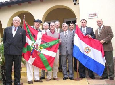 Jasone Euskal Etxeko zuzendariak, erdian, ikurrinaren eta Paraguaiko banderaren artean, Galo Eguez elkarteko presidentea dagoela