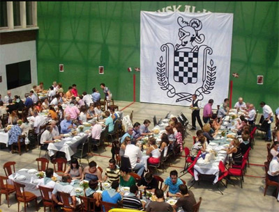View of the Basque club's fronton with tables full of diners and the Baztan insignia