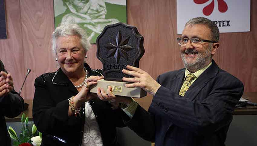 La  bibliotecaria y escritora Arantzazu Amezaga sostiene el premio junto a Koldo Viñuales, de Irujo Etxea (foto Noticias de Navarra)