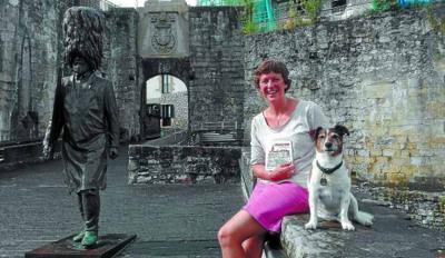 Alex Hallatt posa contenta con su libro y con su perro 'Billie' junto a la escultura del hachero (foto Edu MendibilDV)