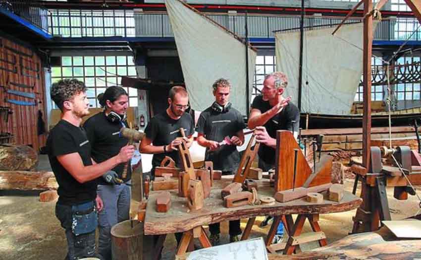 Cuatro de los estudiantes de la escuela de carpintería de ribera atienden las explicaciones de su profesor, Brian McClellan, en el denominado Teatro del Mar, donde se construyen embarcaciones tradicionales (foto Mikel Fraile-DV)