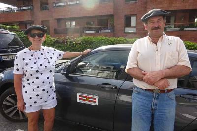 Los Echeharay junto al coche que han conducido en Euskal Herria, en el que se aprecia el logo de su empresa con la ikurriña (foto EuskalKultura.com)