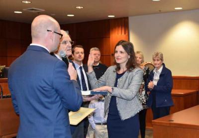 Diana Lachiondo jura su cargo, con su padre, Dave Lachiondo sosteniendo el ejemplar sobre el que jura